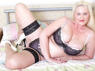 fair-haired nice courtesan enjoys playing with a glass large strapon